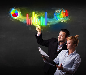 Young business couple touching colorful modern graph system conc