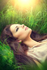 Beauty woman lying on the field and dreaming. Enjoying nature
