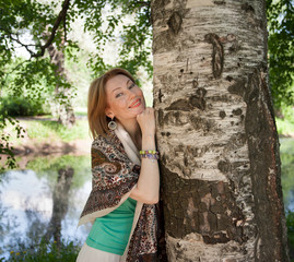 beautiful woman at a tree in summer
