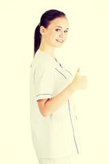 Young female doctor or nurse gesturing OK