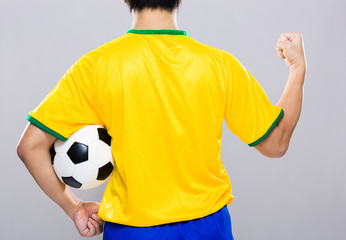 Back view of man hold soccer ball and fist up