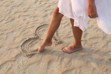 leg girl draws in the sand heart