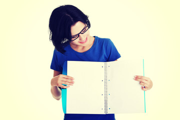 Young woman showing blank pages of her notebook