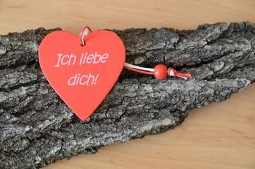 Ich liebe dich - Aufschrift auf rotem Herz aus Holz