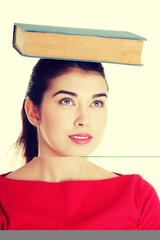 Young caucasian woman with book on her head