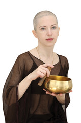 Bald woman in brown with singing bowl, meditating
