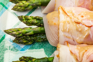 Asparagus wrapped in chicken and bacon in a baking dish