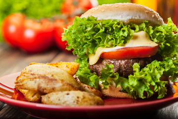 Closeup of cheeseburger with fries potatoes