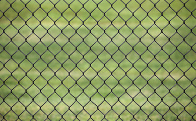 Metal fence with Green grass field background for protection