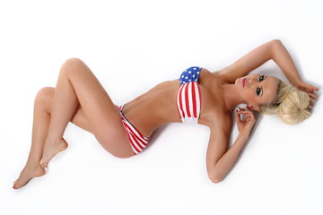 Sexy blonde young woman posing in a stars and stripes bikini