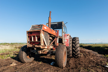 old tractor parked in a peat bog field