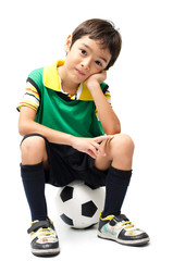 Little boy sitting on football on white background