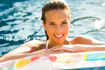 Beauty girl relaxing in pool using mattress