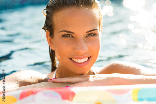 canvas print picture Beauty girl relaxing in pool using mattress