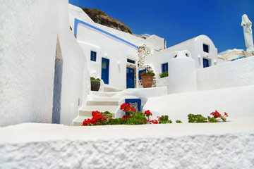 white - blue Santorini traditional architecture with flowers