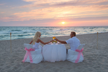 Couple at beach romantic dinner with candles