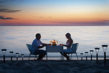 A young couple share a romantic dinner with candles