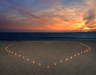 candles heart at sandy sea beach against bright sunset