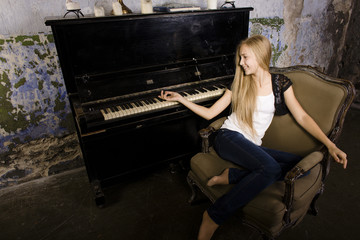 young blond girl playing on piano