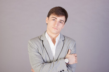 Young businessman looking confidently on gray background