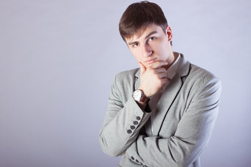 Young businessman in a jacket thinking on a gray background