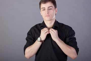 Young man buttons black shirt on a gray background