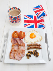 cooked english breakfast with british flag and tea