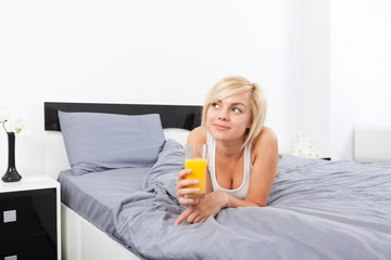 woman drink orange juice, lying on bed
