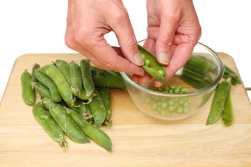 Hands shelling peas