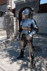 knight in the ancient metal armor standing near the stone wall