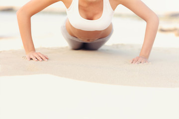 Woman doing push-ups at the beach