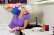 Silly woman holding spray cleaner to her head