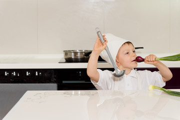 Little boy dressed as a chef playing