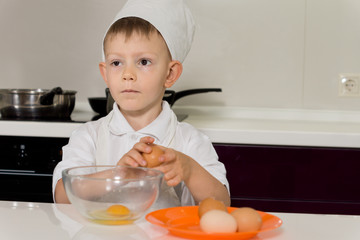 Young chef breaking eggs into bowl