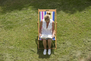 Woman sitting on a deck chair reading a book