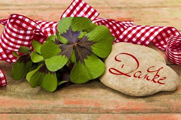 Kleeblätter, Geschenkband und Stein auf Holz, Danke