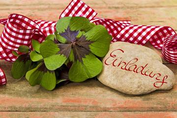 Kleeblätter, Geschenkband und Stein auf Holz, Einladung