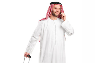 Arabic sheik talking on phone and carrying a luggage