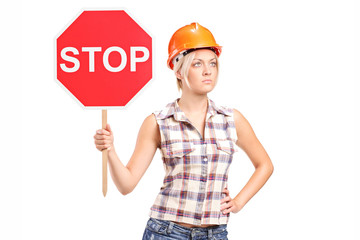 Female construction worker holding a stop sign