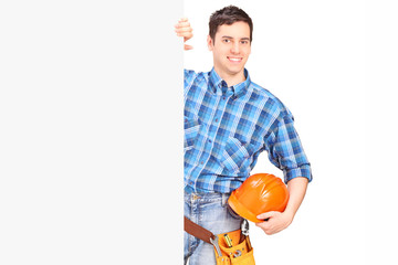 Male construction worker standing behind blank panel