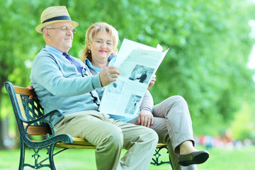 Mature man and woman reading the news outdoor