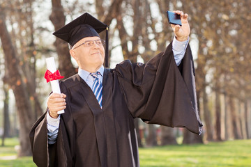 Mature man holding diploma and taking selfie in a park