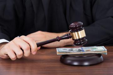 Judge Striking Gavel On Banknotes At Desk