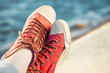 red trendy sneakers on girl and seascape as background