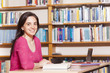 Smiling female student studying in a library