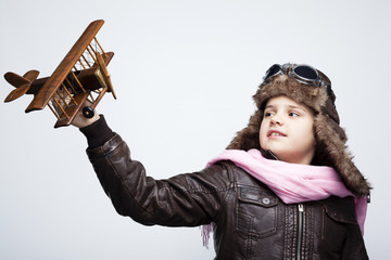 Happy child playing with toy airplane against gray background