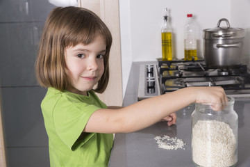 girl putting rice in a glass container
