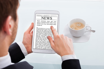 Businessman Reading News On Digital Tablet At Desk