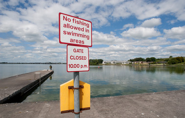 no fishing allowed in swimming area sign by a lake pier