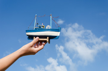 female hand hold wooden ship toy on sky background